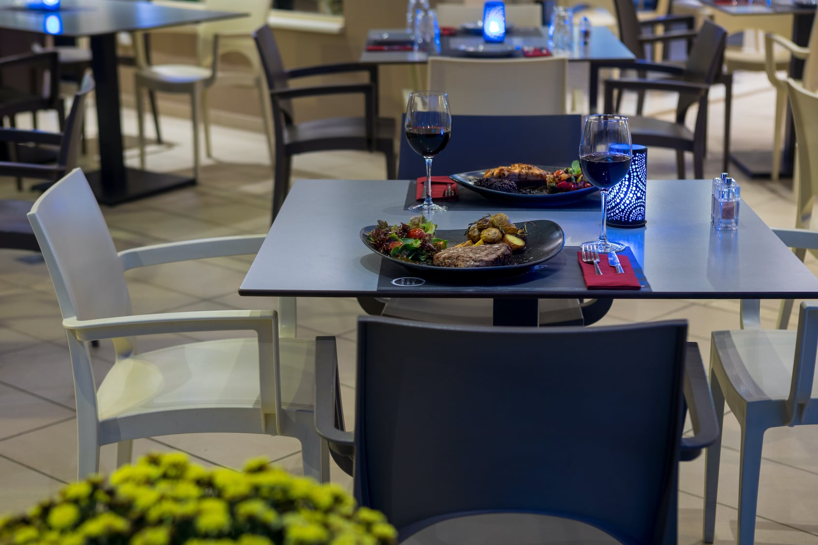 A plate with grilled meat, salad and glasses with wine in the Valentino Pasta & Grill.